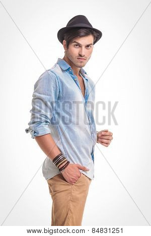 Side view of a handsome casual man looking at the camera while holding one hand in his pocket.