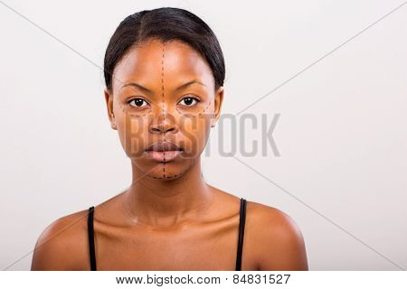 pretty african woman face marked with lines for cosmetic surgery