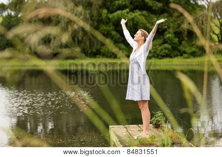 beautiful young woman with arms outstretched by the lake outdoors