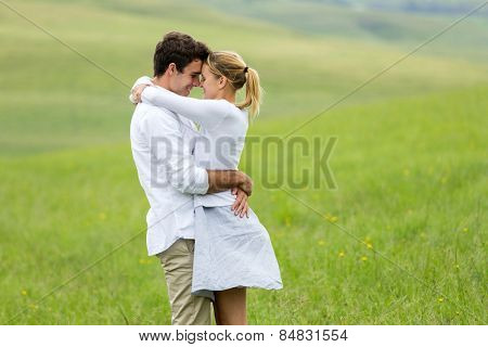 happy young couple embracing outdoors