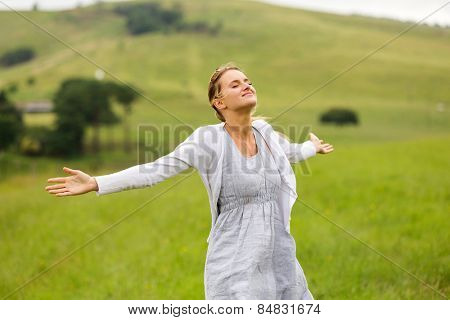 smiling young woman with arms open on grassland