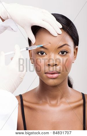 cute african woman receiving cosmetic injection on her forehead