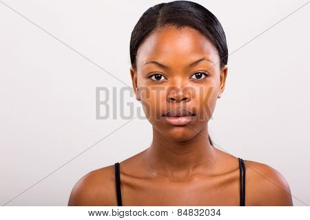 cute african american girl without makeup on plain background
