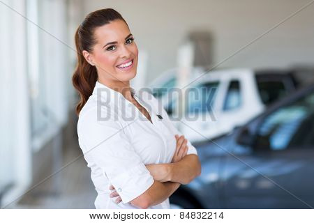 portrait of beautiful vehicle saleswoman with arms folded in showroom