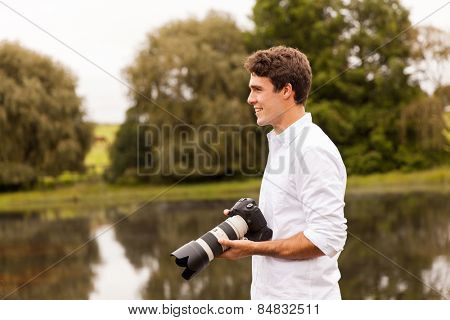 handsome young male photographer with dslr camera outdoors
