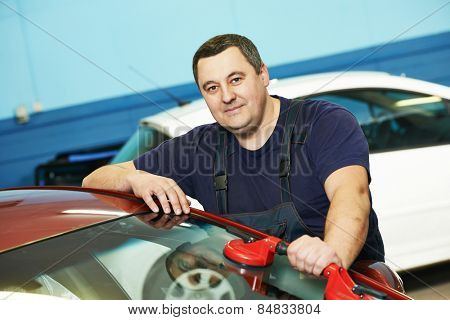 Automobile glazier repairman at  windscreen or windshield repair service shop