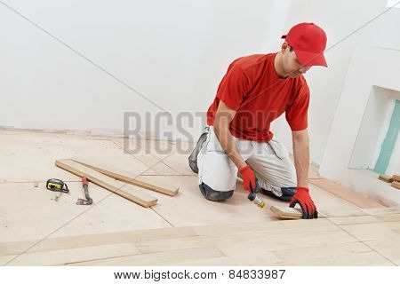 carpenter worker installing wood parquet board during flooring work with hammer