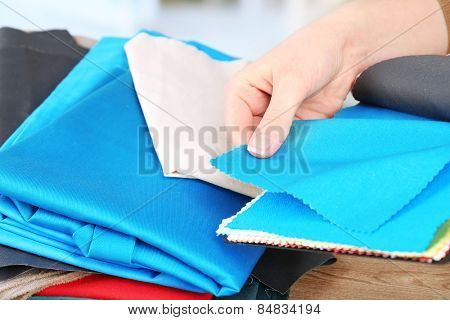 Colorful fabric samples in female hands on wooden table and light blurred background