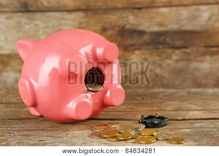 Opened piggy bank with coins on old wooden table