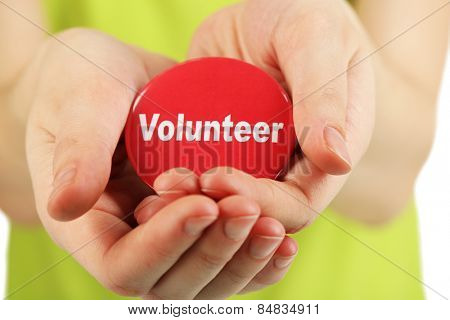 Round volunteer button in hands of girl close-up