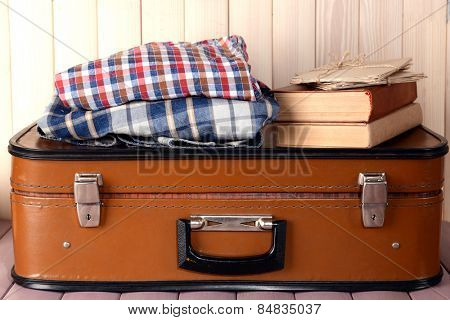 Vintage suitcase with clothes and books on wooden background