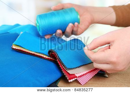 Colorful fabric samples with thread in female hands on wooden table and light blurred  background