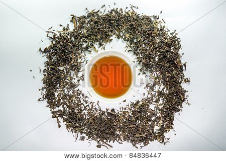 A cup of tea in the center of tea leaf