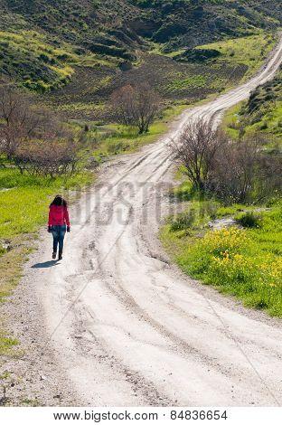 Teenage Girl Walking In A Country Dirt Road