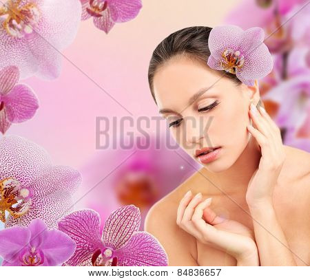 Beautiful young woman with orchid flower in hair on pink orchid flowers background