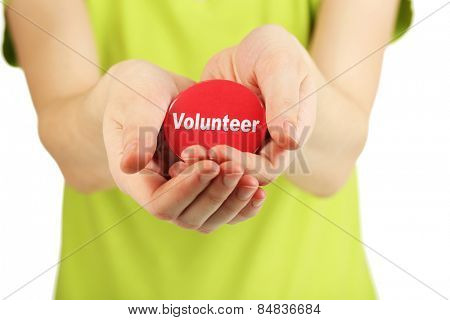 Round volunteer button in hands of girl isolated on white