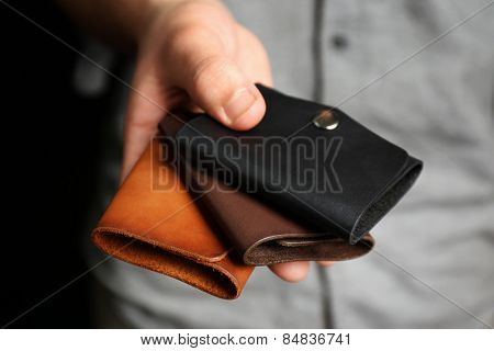 Man holding hand made leather wallets on black background