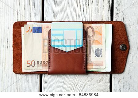 Hand made leather man wallet with money on white wooden background