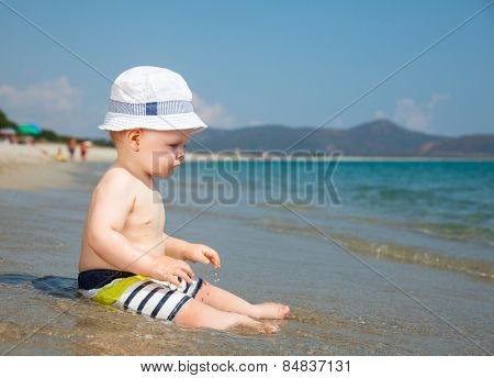 Baby boy wearing hat and shorts playing on a beach