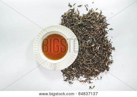 A white cup of tea and dried tea leaf