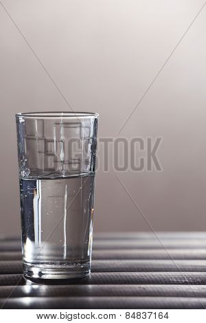 Glass of clean mineral water on wooden planks surface and light background