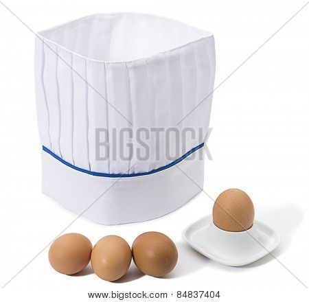 Eggs in front of chef's hat isolated on white background.