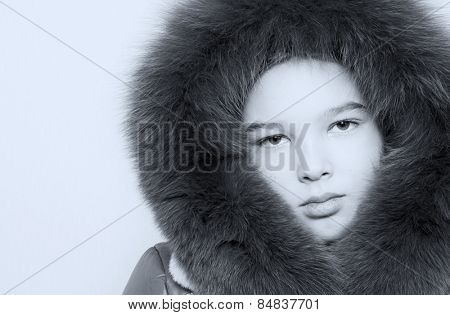 Toned portrait of a girl in a fur hat