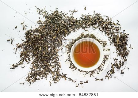 White cup of tea with dried tea leaf on the white background
