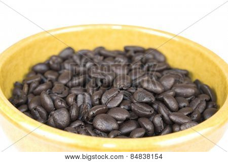 Roasted coffee beans close up in a yellow bowl