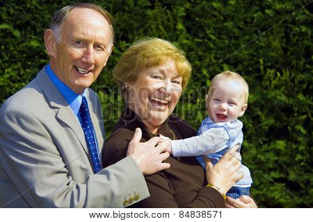 Smiling grandparents holding happy baby boy portrait