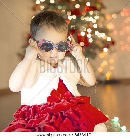 Little girl with sun glasses near the Christmas tree