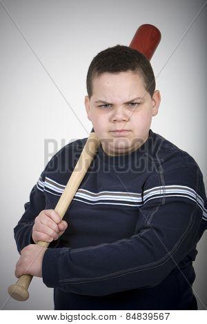 Young hispanic boy threatening with a baseball bat