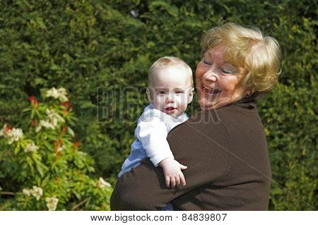 Happy grandmother holding grandson in garden