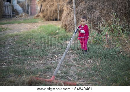 Little Country Girl Working With A Rake