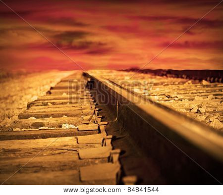 Train tracks fading towards the horizon at sunset