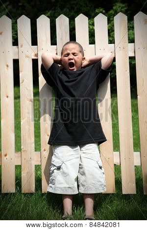 Tired latino boy yawning outside