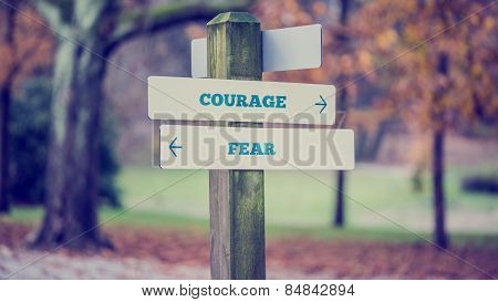 Rustic Wooden Sign In An Autumn Park With The Words Courage - Fear