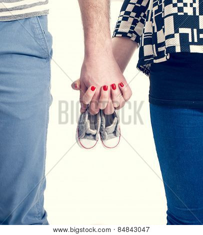 Future Parents Holding Hands And A Pair Of Little Shoes Over White Background