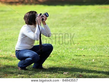 Pretty woman crouching with camera outdoors