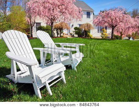 Adirondack chairs sitting on grass in front of generic colonial style New England house