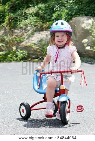 Cute young girl standing on her small bike