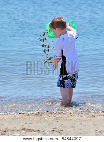 Boy playing with sand at the beach