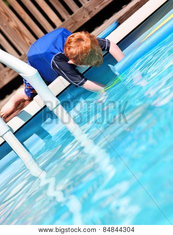 Young redheaded boy relaxing by pool wearing a flotation vest for safety