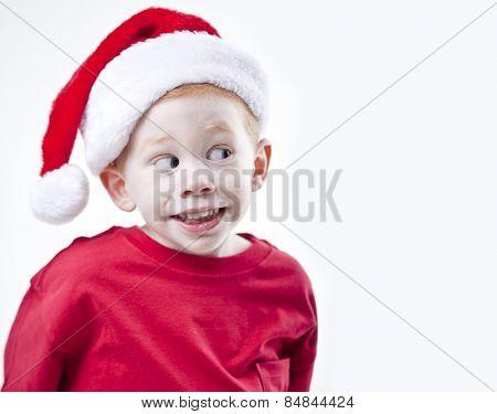 Cute boy looking sideways wearing a Christmas santa hat