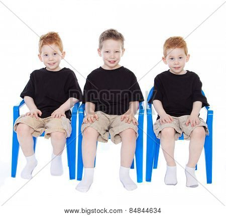 Three boys sitting on blue chairs on white