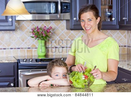 Beautiful mother and son mixing a salad in the kitchen