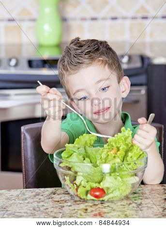 Young boy in kitchen mixing a salad in a bowl