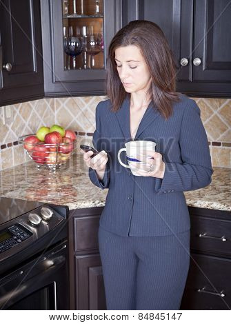 Young businesswoman checking her cell phone in kitchen