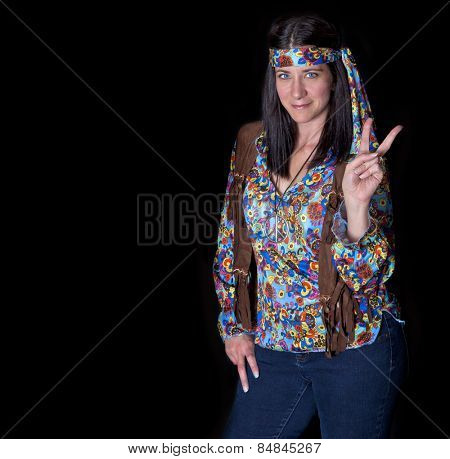 Hippy girl giving peace sign on black background