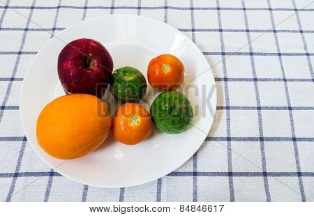 Six Mixed Fruits And Vegetables With Kaffir Lime On White Plate Placed On Squared Background